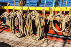 Coiled rope lines. Stored on belaying pins  on a wooden tall ship Stock Photo