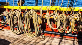 Coiled rope lines. Stored on belaying pins  on a wooden tall ship Royalty Free Stock Photography