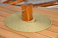 Coiled rope on teak deck Royalty Free Stock Image