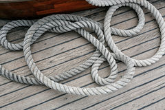 Coiled rope on a wooden deck. Overhead view of neatly coiled rope on a wooden deck Stock Photos