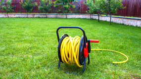 Coiled rubber yellow hose on grass. Coiled rubber garden yellow hose on grass Royalty Free Stock Image