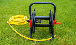 Coiled rubber yellow hose on grass. Coiled rubber garden yellow hose on grass Royalty Free Stock Images