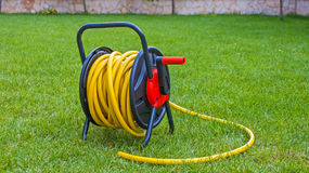 Coiled rubber yellow hose on grass. Coiled rubber garden yellow hose on grass Stock Photo