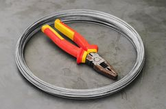 Coiled steel wire over a stone table with a used red plier on ce. Nter. Carpentry and construction tools Stock Image