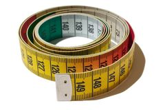 Coiled tape measure. A tape measure isolated on a white background Royalty Free Stock Image