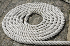 Coiled White Rope Detail 1. Detail shot of a coiled white rope in a harbor, used as a ship tie-down Stock Photos