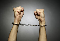 Coils. A man hands  with handcuffs  on black background Stock Images