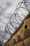 Coils of barbed wire over a concrete fence Stock Images
