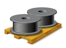 Coils with a black cord are on a wooden pallet. Royalty Free Stock Image
