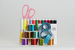 Coils with color threads, sewing needles, scissors. Coils with color strings of various color, sewing needles, scissors and sartorial centimeter Stock Photos