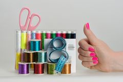 Coils with color threads, sewing needles, scissors. Coils with color strings of various color, sewing needles, scissors, sartorial centimeter and female hands Royalty Free Stock Images