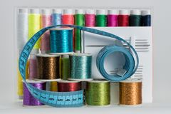 Coils with color threads, sewing needles, scissors. Coils with color strings of various color, sewing needles and sartorial centimeter Royalty Free Stock Photography