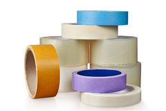 Coils of plastic and paper adhesive tape, on  white. Office scotch tape, packaging tape and paper paint tape isolated on white background, with saved clipping Stock Images
