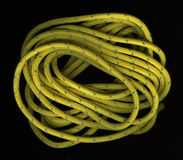 Coils of yellow, nylon rope on black. Loose coils of yellow, nylon rope wit a reflective, silver thread on black background Stock Photo