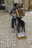 Coimbra, Portugal, June 11, 2018: Street musician with a dog pla Royalty Free Stock Photography