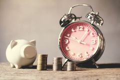 Coin with alarm clock piggy bank on old wood  background Stock Image