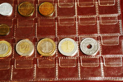 Coin album collection from different countries. And ages with human kid hands Stock Image