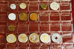 Coin album collection from different countries. And ages with human kid hands Stock Photo