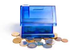 Coin bank. Concept of a house (coin bank) and a lot of golden coins isolated on white background royalty free stock photos