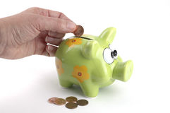 Coin Bank. Female hand putting a penny in a coin bank Stock Images