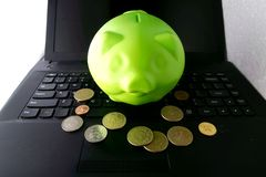 Coin bank and coins on a computer keyboard Royalty Free Stock Photo