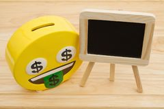 A coin bank on a desk with chalkboard. A coin bank on a desk with blank chalkboard for your message stock photos