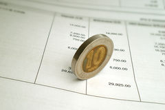 Coin on Bank Statement. An old coin on a bank statement Royalty Free Stock Images