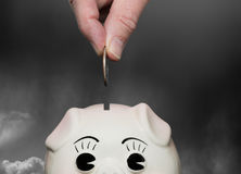Saving money in piggy bank with fingers Royalty Free Stock Photography