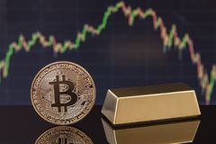 Coin Bitcoin and gold bullion, against background of the exchange graph. Royalty Free Stock Photos
