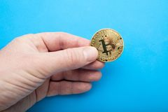 Coin bitcoin in hand, close-up royalty free stock images