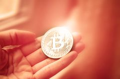 Coin bitcoin in the hands of the girl at the window. With blur and toning. The concept of crypto currency Royalty Free Stock Photos