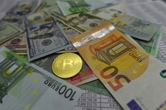 Coin bitcoin lies on banknotes and sheets with numbers. Coin bitcoin lies on banknotes euro, dollars, hryvnias and sheets with numbers Stock Photography