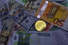 Coin bitcoin lies on banknotes and sheets with numbers. Coin bitcoin lies on banknotes euro, dollars, hryvnias and sheets with numbers Royalty Free Stock Images