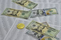 Coin bitcoin lies on banknotes and sheets with numbers. Coin bitcoin lies on notes dollars and sheets with numbers Stock Photos