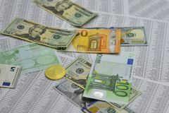 Coin bitcoin lies on banknotes and sheets with numbers. Coin bitcoin lies on notes euro, dollars and sheets with numbers Stock Image