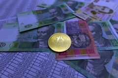 Coin bitcoin lies on banknotes and sheets with numbers. Coin bitcoin lies on notes hryvnias and sheets with numbers Stock Image