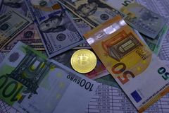 Coin bitcoin lies on banknotes and sheets with numbers. Coin bitcoin lies on banknotes euro, dollars, hryvnias and sheets with numbers Royalty Free Stock Image