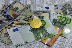 Coin bitcoin lies on banknotes and sheets with numbers. Coin bitcoin lies on euro notes, dollars and sheets with numbers Royalty Free Stock Photos