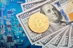 The coin of bitcoin lies on dollars against the background of the video card. The gold coin of bitcoin lies on dollars against the background of the video card Stock Photo