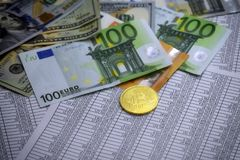 Coin bitcoin lies on banknotes and sheets with numbers. Coin bitcoin lies on euro notes, dollars and sheets with numbers Stock Image