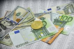 Coin bitcoin lies on banknotes and sheets with numbers. Coin bitcoin lies on euro notes, dollars and sheets with numbers Royalty Free Stock Photography