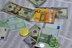 Coin bitcoin lies on banknotes and sheets with numbers. Coin bitcoin lies on notes euro, dollars and sheets with numbers Stock Photos