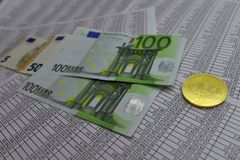 Coin bitcoin lies on banknotes and sheets with numbers. Coin bitcoin lies on notes euro and sheets with numbers Royalty Free Stock Photos