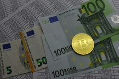 Coin bitcoin lies on banknotes and sheets with numbers. Coin bitcoin lies on notes euro and sheets with numbers Stock Photo