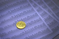 Coin bitcoin lies on sheets with numbers. Coin bitcoin lies on sheets with figures in tables. btc. bitcoin Stock Photos