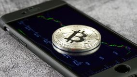 Coin bitcoin, lying on the smartphone, the display of which displays the schedule of quotations of crypto currency. Trade in crypto currency. 4k stock footage