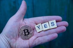 Coin bitcoin and the word yes on the palm of your hand. Large coin bitcoin and word on the open hand palm royalty free stock photos