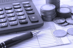 Coin, a calculator, a pen on the business papers. Calculator, a pen on the official papers of the budget calculations