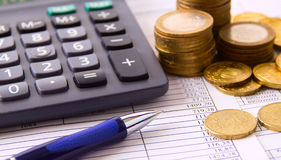 Coin, a calculator, a pen on the business papers Stock Photos
