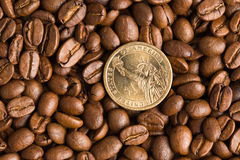 Coin on coffee beans background Stock Images
